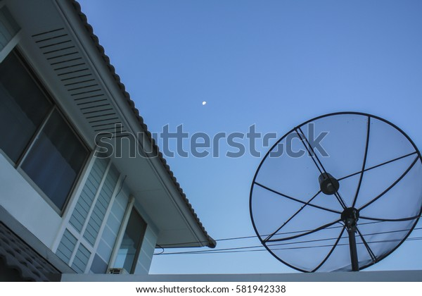 Satellite dish on the roof,blue sky with part of the moon