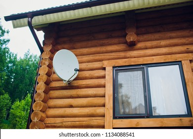 Satellite dish on the wall of the house. Antenna is white. The house is made of wooden beam of brown color. Close-up. No one in the picture.