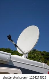 Satellite dish with sky on roof of camper van