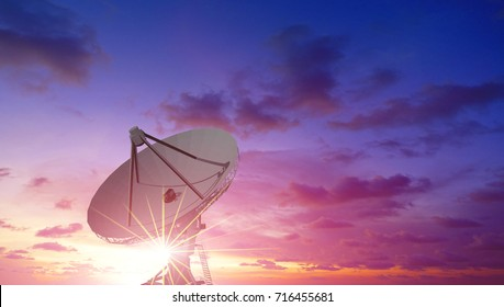 Satellite dish with sun flare effect and sunrise sky background