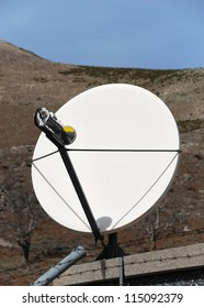 Satellite dish in the sun on top of a mountain
