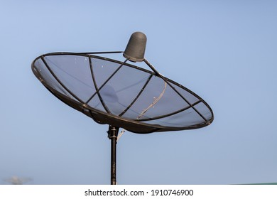 A satellite dish waiting to receive a TV signal. Blue sky background