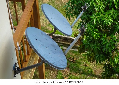 Satellite dishes on apartment brick wall.A satellite dish is a dish-shaped type of parabolic antenna designed to receive or transmit information by radio waves to or from a communication satellite.