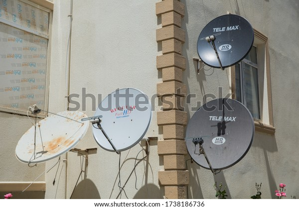 Satellite dishes on the old house. Satellite TV on the wall of a multistory building . Satellite dish antennas . A bird sit at the satellite dish with other dishes . Azerbaijan Baku 20.05.2020 .