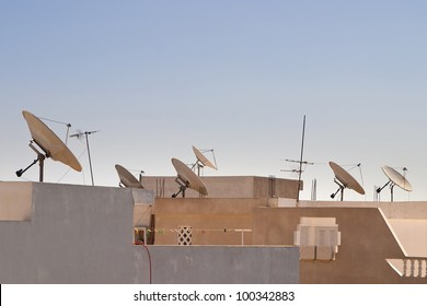 Satellite dishes on rooftop in Tunisia. Pointing in the same direction with a blue sky in the background.