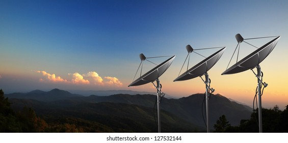 Satellite dishes on summit with sunset.