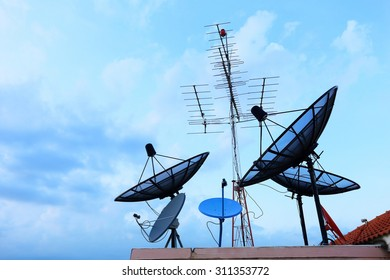 Satellite Dishes and TV antennas on the house roof with a beautiful blue sky