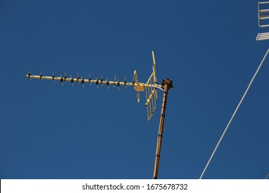 Satellite and television antennas on the roof against a blue sky