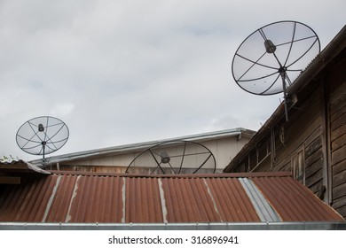 Satellite TV antenna on the roof , Thailand . Old wooden house with a satellite dish . Old houses with zinc roofs Wooden house tin roof ,Old Thai style wooden house with rusty zinc roof