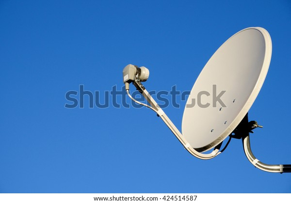 Satellite TV antenna on sky background