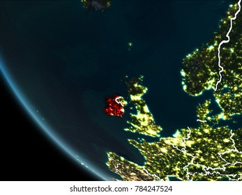 Satellite view of Ireland highlighted in red on planet Earth at night with borderlines and city lights. 3D illustration. Elements of this image furnished by NASA.