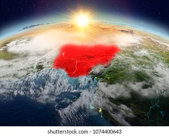 Satellite view of Nigeria highlighted in red on planet Earth with clouds during sunrise. 3D illustration. Elements of this image furnished by NASA.