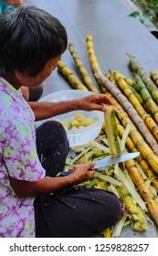 Sateng, Yala/Thailand - April 13 2017: A woman is peeling and cutting sugarcane
