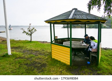 Sater, Sweden July 25, 2020 Asenior couple having a fika or coffee break outside under a pagado in the rain.