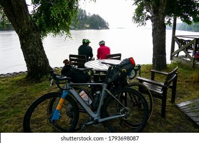 Sater, Sweden July 25, 2020 Bicyclists taking a break in the rain near Braviken bay.