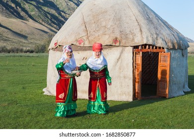 Sati, Kazakhstan – September 07, 2016: Two Kazakh women in traditional clothes in front of a yurt welcoming guests with candies, For editorial Use only, Sati village, Tien Shan Mountains, Kazakhstan