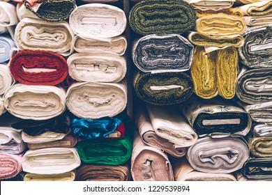 Satin drapery fabric rolls in a fabric shop shelf