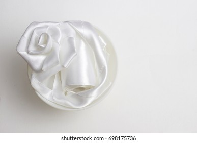 Satin ribbon white rose isolated on white background. Handmade handicrafts concept