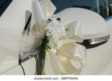 Satin scarves and flowers decorated on the wedding car. Wedding concept of decorating vehicles