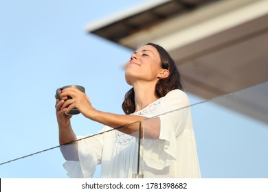 Satisfied adult woman with coffee cup breathing fresh air on a hotel balcony at summer
