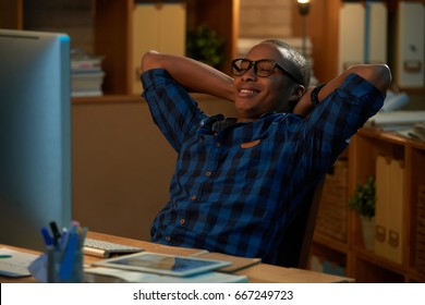Satisfied African American businessman in eyeglasses holding hands behind head while enjoying results of accomplished work, interior of modern open plan office on background