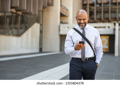Satisfied african businessman using smartphone while walking in the street. Mature smiling business man walking on the road and messaging with phone. Happy successful entrepreneur going to work.