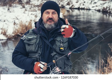 Satisfied angler on the bank of a winter river.