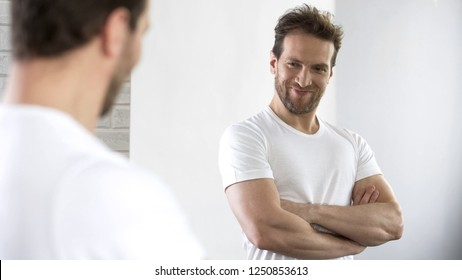 Satisfied with beautiful sports figure male examining his reflection in mirror