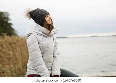 Satisfied beautiful woman with cute smile and closed eyes sitting on the beach against beautiful sea view and enjoy the warm wind in her face. Good vacations alone with myself. Girl in warm hat jacket