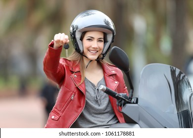 Satisfied biker showing motorbike keys on her scooter on the street