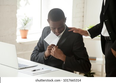 Satisfied black businessman hiding envelope into suit pocket receiving bribe from white corrupt partner holding his shoulder, happy promoted african american employee getting money bonus from boss