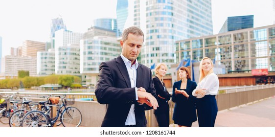 Satisfied businessman looking at watch in La Defense Paris,  . Concept of time management and biz.