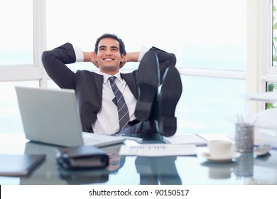 Satisfied businessman relaxing in his office