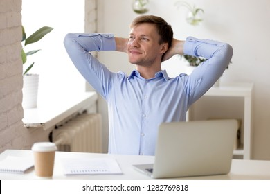 Satisfied businessman relaxing leaning back with hands behind head, enjoying break at workplace, happy man thinking about successful business project, strategy, finish work with laptop, dreaming