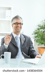 Satisfied businessman sitting at desk with laptop on it, holding pen in hand, looking at camera, smiling.