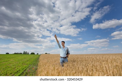 Satisfied businessman standing in golden barley field with laptop and raised arm