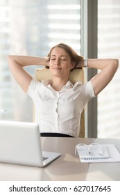 Satisfied businesswoman leaning back in chair and relaxing at the desk with hands behind head. Lady dreaming about business success with closed eyes. Short break during hard work day