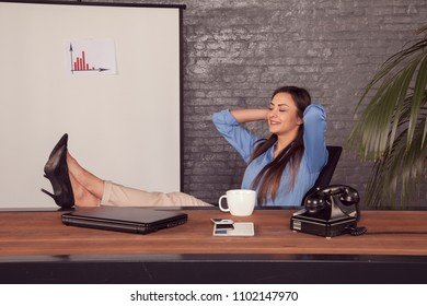 Satisfied businesswoman, sitting in the office and dreaming about the future