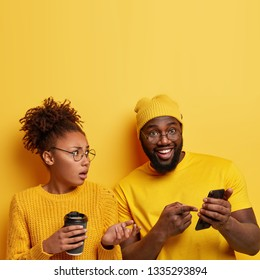Satisfied cheerful black man points at screen of cell phone, shows funny photos to girlfriend, demonstrates meme, connected to wireless internet, puzzled woman gestures actively and holds coffee