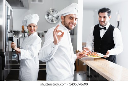 Satisfied cheerful positive male chef approving dish in kitchen of fish restaurant before serving guests