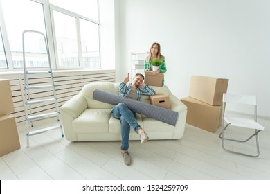 Satisfied cheerful young couple strong man and pretty woman holding their things in their hands sitting in the living room of a new apartment. Housewarming concept.