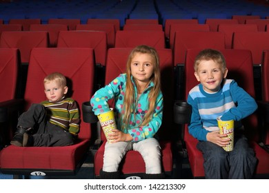 Satisfied children watching a movie and eating popcorn in the cinema