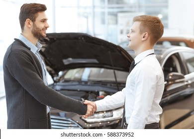 Satisfied client. Professional car salesman shaking hands with his cheerful male client after selling him new car buying car rental service business deal agreement handshake professionalism lifestyle
