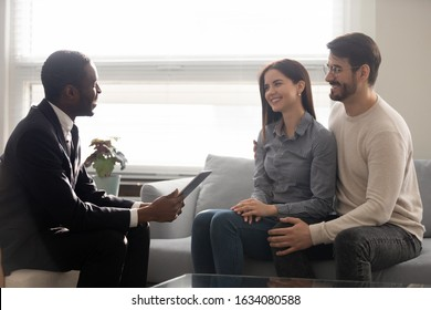 Satisfied clients and estate agent sitting on couch, couple family listens African realtor explain buying process using tablet for presentation, discuss future profitable deal with potential customers