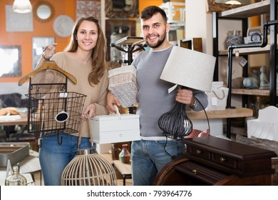 Satisfied couple demonstrating their buies in shop of secondhand furniture