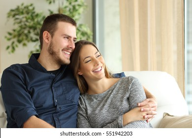 Satisfied couple of householders sitting on a sofa and looking through the window of the living room at home