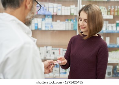 Satisfied customer buying medicaments in drugstore. Mature pharmacist offering woman medical products, giving blister pack of pills. Beautiful woman choosing remedy for health care.