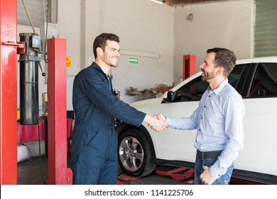 Satisfied customer shaking hands with car mechanic at auto repair shop