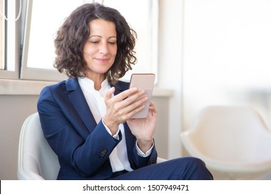 Satisfied customer using online mobile app. Business woman sitting in armchair, using mobile phone, looking at screen and smiling. Digital technology concept