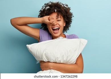 Satisfied dark skinned glad curly woman wakes up with pillow and feather, rubs eyes, dressed in homewear, being in good mood after healthy sleep, isolated over blue background. Sleeping concept